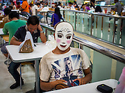 """07 FEBRUARY 2015 - BANGKOK, THAILAND:   A young man wears a mask from the movie """"The Purge: Anarchy"""" in a mall foodcourt in Bangkok, Thailand.  PHOTO BY JACK KURTZ"""