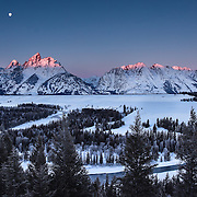 A full moon shines during first light upon the Grand Tetons, overlooking the Snake River.