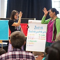 """Pauletta Chief-Lee, left, and Stephanie Littlehat make the sign for """"dad"""" in sign language, Wednesday, Nov. 13 at the Octavia Fellin Public Library Children's Branch during Shimá Storytelling."""