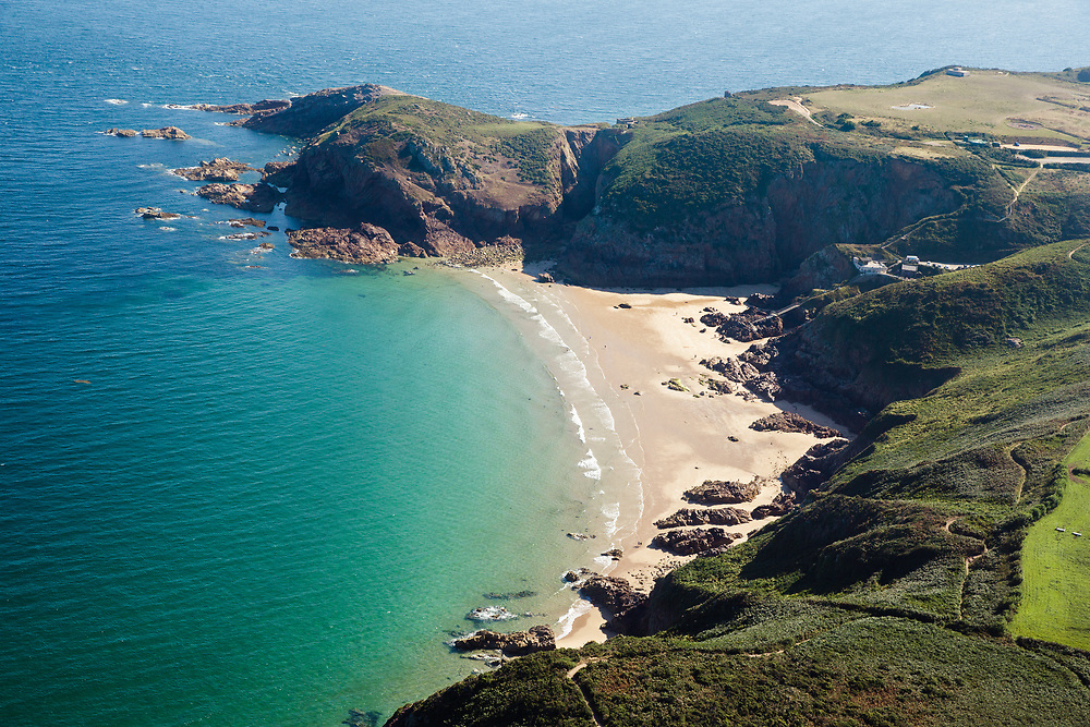Aerial view of the turquoise, calm water at Plemont beach on a sunny sumers day in Jersey, Channel Islands