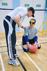 Coach talking to a Team member during a Goalball game; a threeaside game developed for the visually impaired and played on a volleyball court, A specially adapted ball containing an internal bell is used,