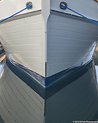 Bow and mooring lines of white wooden boat at moorage in Sacramento Delta with reflection in water