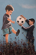a young boy playing with a caricature on a wall
