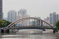 people crossing small bridge over wusong, a tributary of the huanpu, in Shanghai China