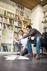 Two businessmen looking at notes in an office, Bavaria, Germany