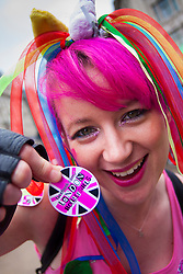 London, June 28th 2014. A woman offers a London Rollergirls sticker as the Pride London parade proceeds through the city's streets.