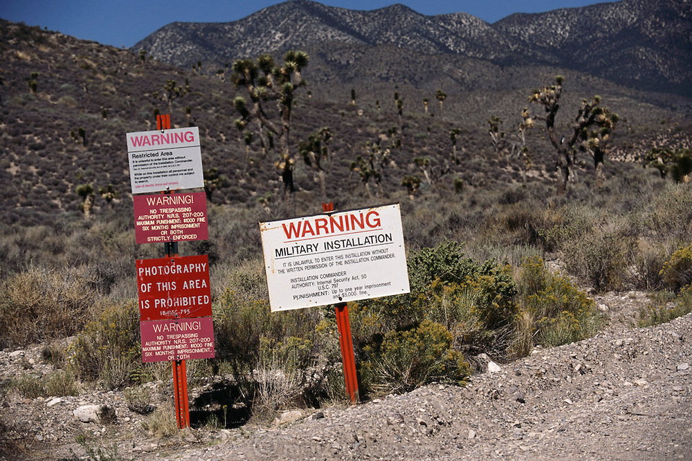 Area 51 signs on government land in Nevada warn visitors against trespassing and photography under penalty of imprisonment. Speculation that aliens were brought to the site and hidden by the US government has turned it into a tourist attraction although it is many miles on unmarked dirt roads off of Nevada Highway 360. (1999).