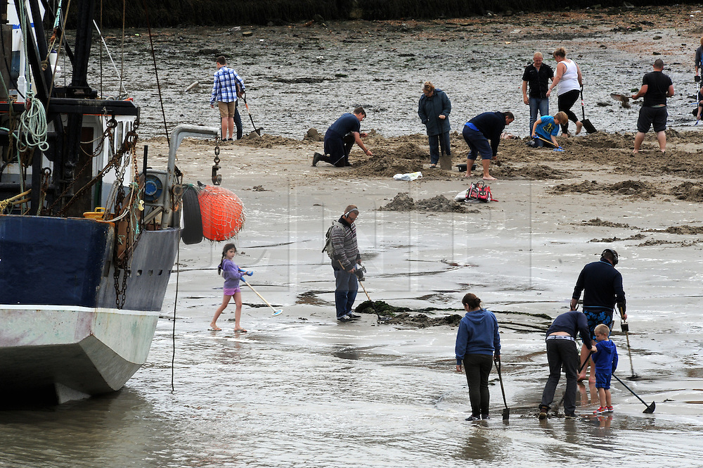 """© Licensed to London News Pictures. 30/08/2014<br /> Gold diggers are still out digging for gold at Outer Harbour Beach in Folkestone,Kent at 7pm tonight (30.08.2014). <br /> £10,000 of buried treasure at Outer Harbour beach near Sunny Sands, Folkestone,Kent.<br /> The installation, entitled """"Folkestone Digs"""", is funded by Bristol-based designers Situations and the idea for the project came from Berlin-based artist Michael Sailstorfer.<br /> The small gold bars - similar to a dog tag - come in two sizes, worth around £250 and £500.<br /> <br /> (Byline:Grant Falvey/LNP)"""