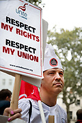 Food service industry workers strike for higher wages on October 4th 2018 in Leicester Square, London, United Kingdom. Day of action by workers from TGI Fridays, McDonalds; Deliveroo and Wetherspoons, supported by TUC and Labour Party, demanding better conditions for the hospitality sector. A chef holds a Unite trade union placard saying Respect my rights.
