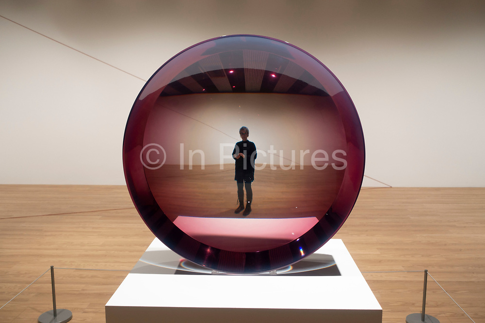 Visitors interacting with artworks at the Space Shifters exhibition at the Hayward Gallery on 16th December 2018 in London, United Kingdom. The exhibit was a major group show of sculptures and installations that explored perception and space, featuring 20 artists. Untitled Parabolic Lens 1971 by Fred Eversley.