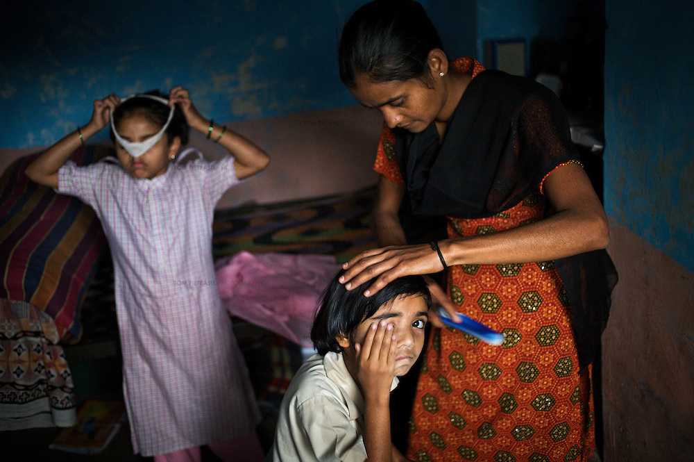 """Vasanti Shinde, age 26, who is HIV positive, at home with her daughters Vrinda, 8 and Shruda, 10. Shinde works for the Save Foundation which represents the rights of HIV positive people. ...Like many of the women who work for and with the Save Foundation, Vasanti Shinde, age 26, only found out that she was HIV positive after her husband became seriously ill with an AIDS-related illness five years ago. Vasanti's husband subsequently died. Vasanti now lives with her two younger daughters Shrudha, age 10, and Vrinda, 8, in the one-room home of her brother in Sangli city. Vasanti's elder daughter, eleven year old Shubhada is being brought up by her paternal grandmother and sees her mother during holidays. Vasanti knows that Shubhada is HIV negative and Shruda is positive but anxiety over the result means that she refuses to have Vrinda tested for HIV. For a monthly income of Rs.3500, Vasanti works as a field officer and counselor for the Save Foundation. She works in the positive-people's pharmacy for no pay. Her work with the Save Foundation entitles her access to a credit union which provides low interest loans covering medical expenses. Though first-line drugs and homeopathic medicine keep Vasanti healthy, she is prone to infection and recently suffered a bout of influenza. Vasanti is completely open about her HIV status and most of her neighbours know that she is HIV positive. Vasanti says that """"I used to feel like I was going to die. Now, because of the Save Foundation, I feel like I'm going to live."""" ..Photo: Tom Pietrasik.Sangli, Maharashtra. India.August 28th 2008."""