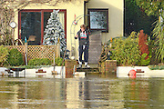 © Licensed to London News Pictures. 05/01/2014. Weybridge, UK. A man takes a photograph from the back garden of a property.  Rising river levels in the River Thames at Weybridge, Surrey, threaten local housing along the river today 5th January 2014. Britain is experiencing flooding and more heavy rain is expected. Photo credit : Stephen Simpson/LNP