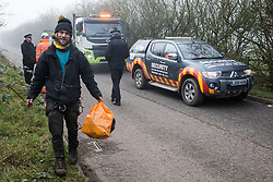 Denham, UK. 6 February, 2020. An Extinction Rebellion activist picks up litter whilst fellow environmental activists block a security vehicle and truck delivering fencing and other supplies to be used for works associated with the HS2 high-speed rail link close to the river Colne at Denham Ford. Works planned in the immediate vicinity include the felling of trees and the construction of a Bailey bridge, compounds and fencing, some of which in a wetland nature reserve forming part of a Site of Metropolitan Importance for Nature Conservation (SMI).
