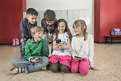 Schoolchildren sitting on floor and looking at cell phone in corridor near lockers, Bavaria, Germany