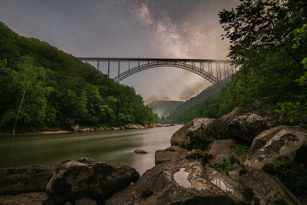 The night comes alive in the New River Gorge as the milky way rises above the iconic arch bridge, the mountain sides exhale plumes of fog and fireflies flitter about between the open air and the tree lined slopes.