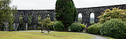 McCaig's Tower rises prominently on Battery Hill overlooking the town of Oban in Argyll, Scotland, United Kingdom, Europe. It is built of Bonawe granite with a circumference of 200 meters with two-tiers of 94 lancet arches. The structure was commissioned by the wealthy, philanthropic banker (North of Scotland Bank), John Stuart McCaig, his own architect. The tower was built between 1897 and his death in 1902, intended as a lasting monument to McCaig's family and as employment for local stonemasons during winter. As an admirer of Roman and Greek architecture, McCaig had planned for an elaborate structure based on the Colosseum in Rome, but only the outer walls were completed. Oban is an important tourism hub and Caledonian MacBrayne (Calmac) ferry port, protected by the island of Kerrera and Isle of Mull, in the Firth of Lorn. This image was stitched from several overlapping photos.