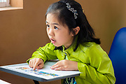 May 2018, Dalat: Little Asian girl student looks up at the teacher for help.