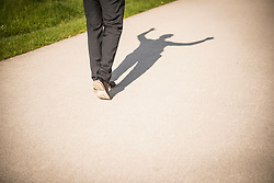 Shadow of low section of man cheering, Munich, Bavaria, Germany