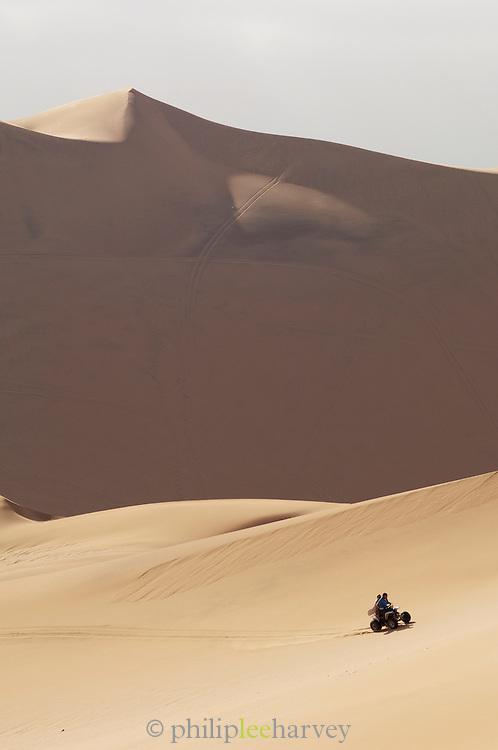 A quad bike driving amongst the sand dunes of the Namib Desert, near Swakopmund, Namibia