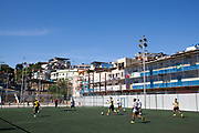 Young people playing football in Vidigal favela, Rio de Janeiro. Since pacification in 2011, Vidigal has slowly become known as what some call a model favela, seen as the safest favela in Rio, home to a mixed community which now includes foreigners, hostels, restaurants, theatres and creative businesses.