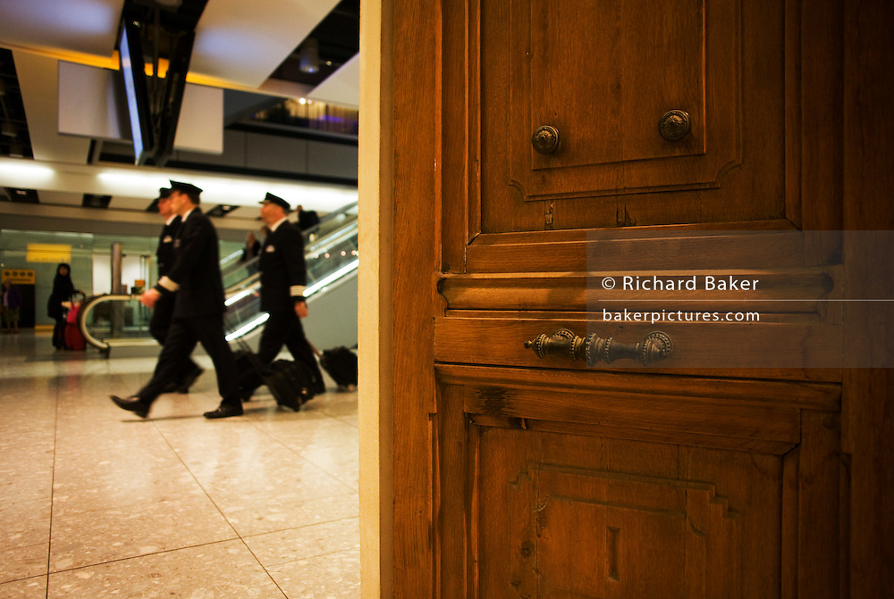 Passing air crew walk past the Paul Smith chateau door at Heathrow airport's terminal 5