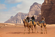 Tourists ride camels, Wadi Rum, Jordan.