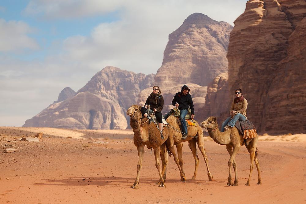 Tourists ride camels, Wadi Rum, Jordan.