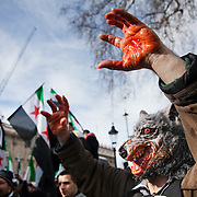 A protestor dressed up as the Big Bad Wolf with bloody hands pretending to be President Assad. An Anti-Assad Syrian demonstration held in Whitehall, Central London. The demonstration was called by the Syrian Community in the UK under the head lines; Syrians are being killed in a genocide and the world is watching. Several hundreds gathered opposite Downing Street 10 calling for Syrians to unite and the world to intervene.
