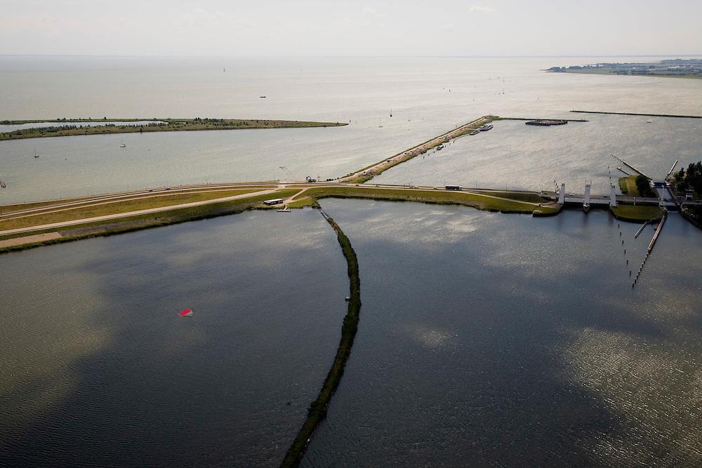 Nederland, Noord-Holland, Enkhuizen, 14-07-2008; spuisluis en schutluis in de Houtribdijk; het oranje-rode object (linksonder) is een waterskischans; de Houtribdijk verbindt Enkhuizen en Lelystad en deelt het IJsselmeer in IJsselmeer en Markermeer; de dijk is oorpronkelijk aangelegd om het Markeermeer in te polderen (Markerwaard), deze inpoldering maakte reeds deeluit van de Zuiderzeewerken; andere namen voor de dijk zijn: Markerwaarddijk, Lelydijk en Dijk Enkhuizen-Lelystad N302; toekomst, algen, licht, leeg, leegte, Lely,. .luchtfoto (toeslag); aerial photo (additional fee required); .foto Siebe Swart / photo Siebe Swart..