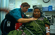 British-born Flight Nurse Barbara Thompson listens to a Native American patient's breathing in the ER at the San Carlos Apache reservation hospital. British-born Barbara has worked as a nurse in the UK and US for 20 years and listens to her patient's lungs with a stethoscope as they poor lady lays back on a gurney with an oxygen line to help her difficulties. San Carlos is a 1.8m acre area of scrub and tiny settlements 100 miles east of Phoenix, Arizona with an 11,000 population, its hospital attracting patients from a radius of 20 miles. By flying her she can have far better specialist care at the Indian Medical Center in Phoenix than can be provided in San Carlos who have only a few doctors and four beds. Native American Air Ambulance (NAAA) is the brainchild of Okalahoma native Cherokee Rick Heape Williams.