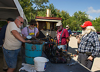 Clem LeGates, Mike Condax and Dave Adams make peach ice cream from a steam engine operating off the steam from Brian Thompson's 1910 Lolly for an afternoon treat during the annual Steamboat Races in Lee's Mills on Thursday.   (Karen Bobotas/for the Laconia Daily Sun)