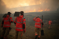 "**2018 Pictures of the year by London News Pictures**<br /> © Licensed to London News Pictures . 27/06/2018 . Saddleworth , UK . Homes are evacuated and a Major Incident is declared as fire-fighters work to control large wildfires spreading across Saddleworth Moor and towards residential areas in surrounding towns . Very high temperatures , winds and dry peat are hampering efforts to contain the fire , described as "" unprecedented "" by police and reported to be the largest in living memory . Photo credit : Joel Goodman/LNP"