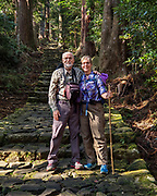 """Tom & Carol on a Kumano Kodo pilgrimage route. Kumano Nachi Taisha shrine was built in homage to Nachi-no-Taki waterfall's kami (spirit god). Don't miss the iconic view of thundering Nachi-no-Taki waterfall (133m, Japan's tallest) paired with Seigantoji pagoda, in Nachikatsuura, Higashimuro District, Wakayama Prefecture, Japan. Kumano Nachi Taisha shrine fuses Buddhist and Shinto influences along the 1000+ year pilgrimage routes of Kumano Kodo. The """"Sacred Sites and Pilgrimage Routes in the Kii Mountain Range"""" form an impressive entry on UNESCO's List of World Heritage Sites. Access: by bus from Nachi Station (20 min) or Kii-Katsuura Station (30 min). Ask driver to stop at base of the Daimonzaka trail (""""Daimonzaka"""" stop); or at the entrance to Nachi Waterfall (""""Taki-mae""""); or at the bus terminus 10 minutes climb below Nachi Shrine (""""Nachi-san""""). Cars can park at Seigantoji Temple. I recommend this remarkably scenic, short walk (3.5 km with 265 meters gain): starting from Daimon-zaka bus stop, ascend a stone-paved path, humbled by massive evergreens, up to the gates of Nachi Taisha shrine; then descend to the falls, at Taki-mae bus stop.  To license this Copyright photo, please inquire at PhotoSeek.com."""