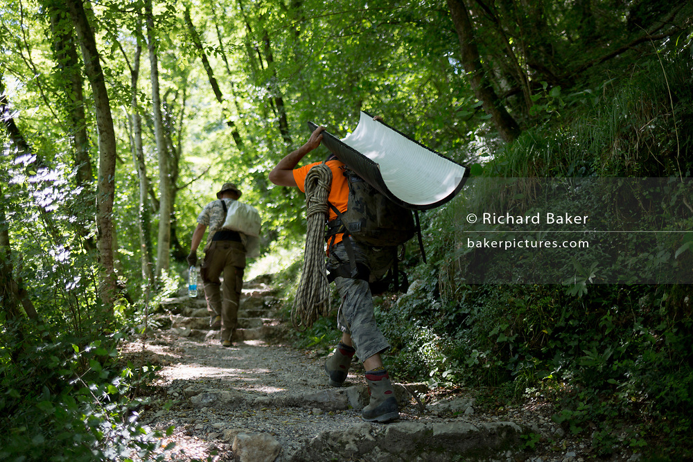 A worker carries materials in the forest at Tolmin Gorge (Tolminska Korita), on 20th June 2018, in Tolmin Gorge , Slovenia.