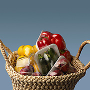 View of shopping basket with plastic-wrapped vegetables and fruit, against blue background, Zukini, Red peppers, Lemons, Red onions, Plums