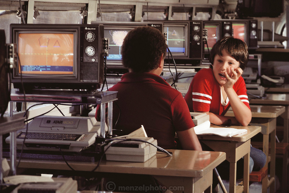 Students seen inside the Napa Computer Bus. In 1983 more than 3,000 school children throughout California's Napa Valley were treated to hands-on experience with ATARI computers. A refurbished school bus with 17 ATARIs on board circulated among the 21 public schools in the district, giving each fourth-, fifth- and sixth-grader several opportunities to work with Atari's PILOT language. An old school bus (circa 1953), provided by the district, was painted red, white and blue and named the Napa Valley Unified School District Computer Lab. The lab accommodated 32 students at a time with each child sharing a 400. Each learning station also included an 11-inch Quasar television for video display and a cassette recorder for storage. The instructor's station was equipped with a disk drive and dot matrix printer as well as a TV and tape recorder. The lab sessions were 45-minutes each and occurred three times within two weeks. (1984)