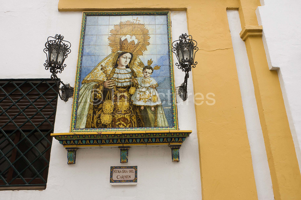 """Andalucian ceramic tiling of the Virgin Mary and baby Jesus on the wall of the Basilica de la Macarena in Seville. Inside the church, the Basilica de la Macarena possesses the most revered image in Seville, """"The Virgin of Hope"""" (Nuestra Señora de la Esperanza) which locals call La Macarena."""
