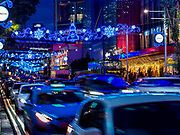 """12 DECEMBER 2018 - SINGAPORE:  Traffic on Orchard Road passes under Christmas lights decorated with Disney characters. Orchard Road is the main shopping district of Singapore and for years hosts a large light display around Christmas. The main sponsor of this year's display is the Disney Company and the displays are decorated with characters from the Disney entertainment universe. This has upset some religious leaders in Singapore and the National Council of Churches of Singapore (NCCS) sent a letter to the Singapore Tourism Board (STB) expressing its concern about the """"increasing secularisation and commercialization of Christmas"""" in Singapore. The STB reached out to the NCCS, but the Orchard Road lights will remain on through the holidays.   PHOTO BY JACK KURTZ"""