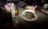 Coffee and cigarette on table at diner.
