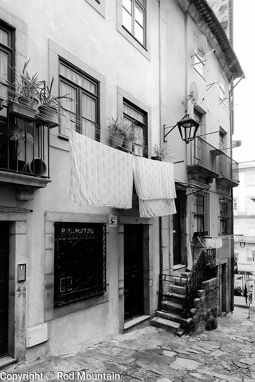 Porto, Portugal - February 13, 2018 - A narrow side street in Porto.<br /> <br /> Image: © Rod Mountain<br /> <br /> http://www.rodmountain.com <br /> <br /> http://bit.ly/RM-archive<br /> <br /> Nikon D800 / Nikkor Lens<br /> @nikoncanada #NikonCA<br /> @NikonUSA #NikonNoFilter<br /> @nikoneurope #NikonEurope<br /> <br /> Instagram<br /> @visitportugal <br /> <br /> FaceBook<br /> @visitportugal <br /> @visitporto.portal<br /> @TurismoPortoNortePortugal<br /> @TurismodePortugal<br /> <br /> Twitter<br /> @visitportugal <br /> <br /> Pinterest<br /> @visitportugal <br /> <br /> http://www.portoenorte.pt/en/<br /> https://en.wikipedia.org/wiki/Porto<br /> https://www.visitportugal.com/en<br /> https://en.wikipedia.org/wiki/Portugal<br /> https://whc.unesco.org/en/statesparties/pt<br /> <br /> #turismoemportugal #turismo #rotaportugal #getlost#explorer #optoutside#createexplore #outforawalk #travelblog #trip #blacknwhitepic #bwmasters #bnwsouls #bnw_zone #awesomebnw #ig_europe #igworldclub #master_shots #exclusive_shots #sidestreet #exploretocreate #streetactivityteam #urbanphotography #urbanandstreet