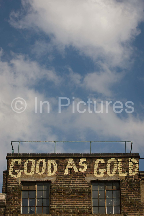 """The words Good as Gold are written on the top of a Victorian building in Southwark, south London. With blue sky and clouds above, we see an urban street message sprayed on the former warehouse near Waterloo. """"Good as gold"""" or """"as good as gold"""" are common English expressions meaning something is genuine or reliable. Referring to people, particularly children, they usually mean well behaved. """"Good as gold"""" is one of numerous figures of speech involving gold as a desirable standard of some kind. The expression is a simile, an analogy used to describe something by comparing it to something else. The word """"gold"""" itself is one of the oldest words in the English language."""