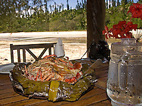 A local specialty, lobsters and veggies, wrapped in banana leaves and baked on coals, underground for hours