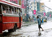 Man with umbrella crosses a flooded street during the monsoon season, Cochin, Kerala, India