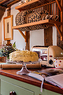 Interior of an English cottage with kitchen with a freshly made cake and exposed ceiling timbers.