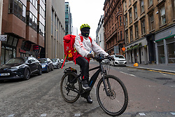 Glasgow, Scotland, UK. 26 March, 2020. Views from city centre in Glasgow on Thursday during the third day of the Government sanctioned Covid-19 lockdown. The city is largely deserted. Only food and convenience stores open. Pictured; A Just Eat delivery cyclist pauses for a portrait. Iain Masterton/Alamy Live News