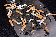 A collection of smoked cigarette ends on a public ash tray outside the British Library, London, United Kingdom.   A smoking ban in England, making it illegal to smoke in all enclosed public places in England, came into force on 1 July 2007 as a consequence of the Health Act 2006.