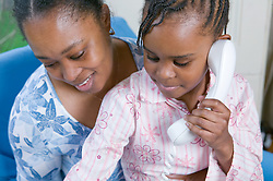Little girl sitting on her mother's lap making a phone call,
