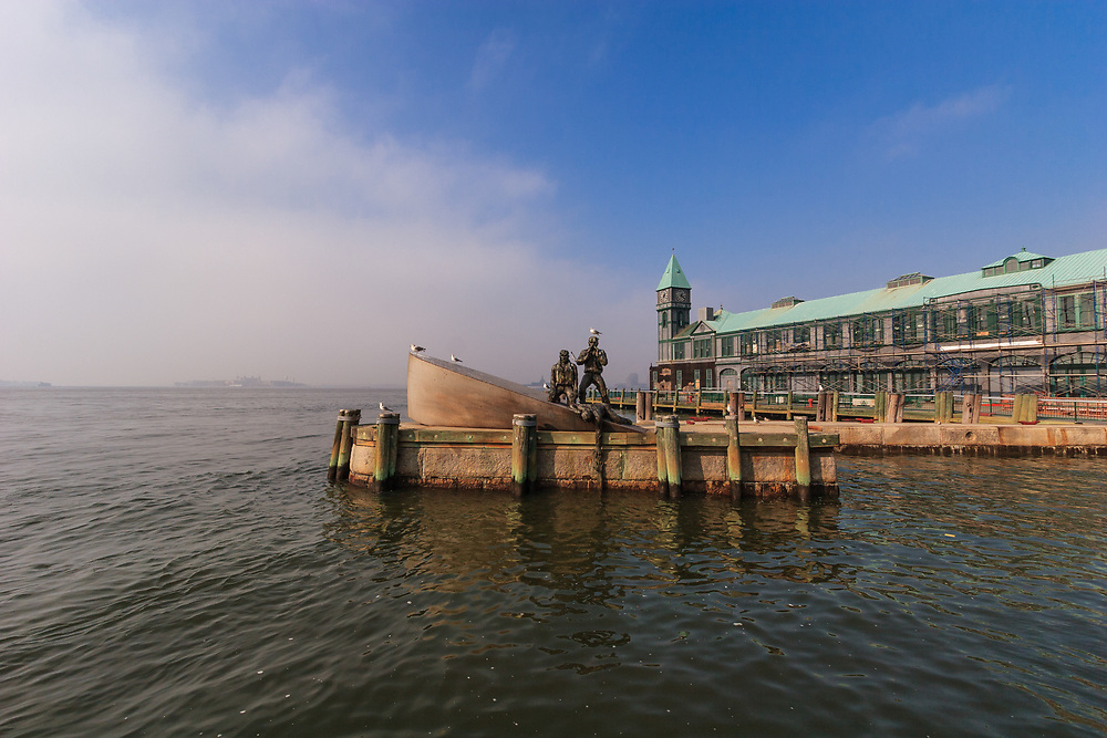 The American Merchant Mariners' Memorial in front of City Pier A in Manhattan,New York City, USA.  The memorial is a representation in bronze of four merchant seamen with their sinking vessel after it had been attacked by a U-boat in World War II.