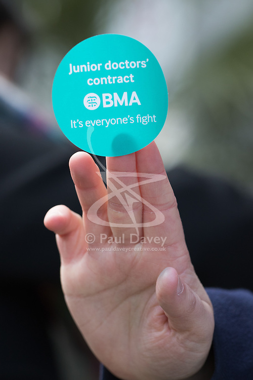 Great Ormond Street Hospital, London, April 26th 2016. A hand offers a sticker in support of the striking junior doctors as they picket outside Great Ormond Street Hospital for Children.