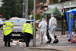 Police and forensics officers at the scene in Claremont Road, Moss Side, Manchester, where several people have been injured after a shooting.